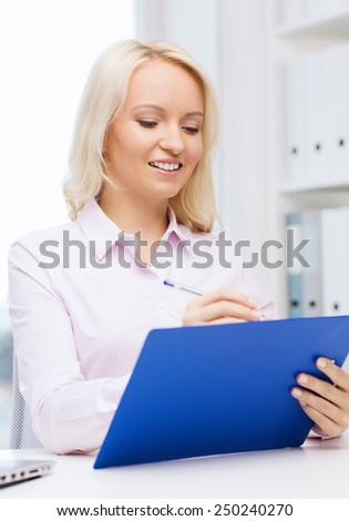 education, business and technology concept - smiling businesswoman or student with clipboard writing and taking notes in office - stock photo