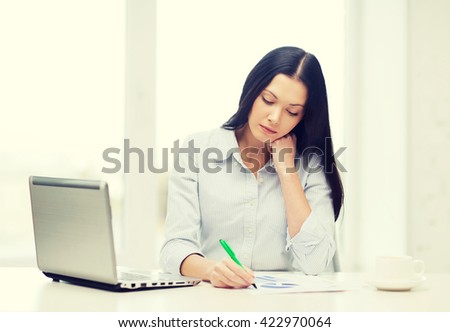 education, business and technology concept - tired businesswoman or student with laptop computer, charts and coffee
