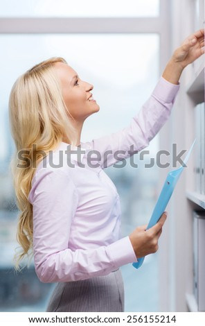 education, business, gesture, success and people concept - smiling businesswoman taking files from shelf in office