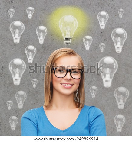 education, business, inspiration and people concept - smiling young woman in eyeglasses having idea over gray background with light bulbs