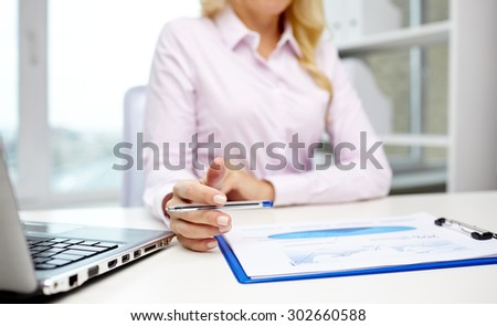 education, business, people and technology concept - close up of smiling businesswoman with laptop computer and papers sitting in office - stock photo