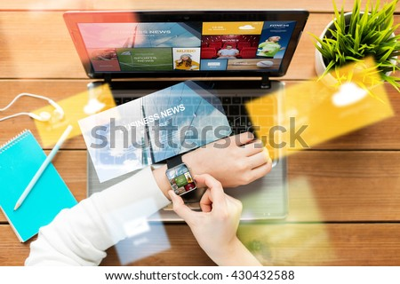 education, business, people, mass media and technology concept - close up of woman with smart watch and laptop computer on wooden table with internet application on screens