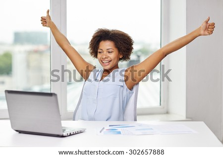 education, business, success, gesture and technology concept - happy african american businesswoman or student with laptop computer and papers showing thumbs up and celebrating triumph at office - stock photo