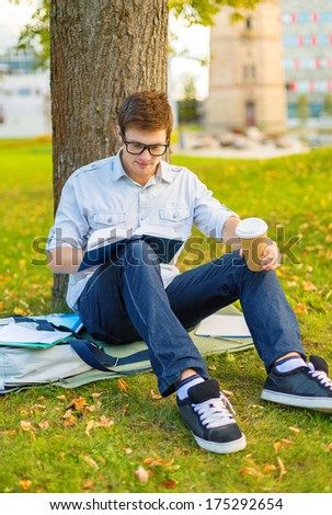 education, campus and people concept - smiling teenager in eyeglasses reading book with take away coffee - stock photo