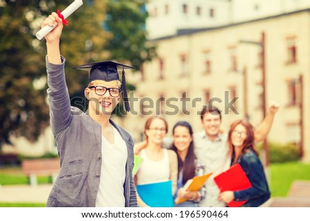 education, campus and teenage concept - smiling teenage boy in corner-cap and eyeglasses with diploma and classmates on the back - stock photo