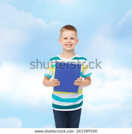 education, childhood and school concept - smiling little student boy with blue book over blue cloudy sky background - stock photo