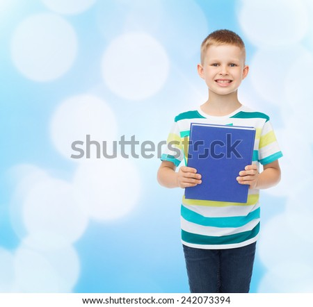 education, childhood and school concept - smiling little student boy with book over blue background - stock photo