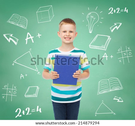 education, childhood and school concept - smiling little student boy with book over green board with doodles background - stock photo