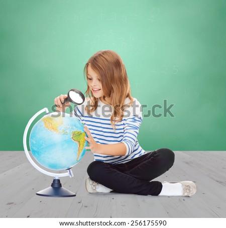 education, childhood, geography and school subject concept - happy little student girl looking at globe with magnifier over green chalk board background - stock photo