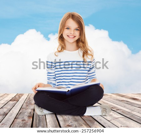 education, childhood, people and school concept - little student girl studying and reading book over blue sky and cloud background - stock photo