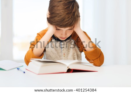 education, childhood, people, homework and school concept - bored or displeased student boy reading book or textbook at home - stock photo