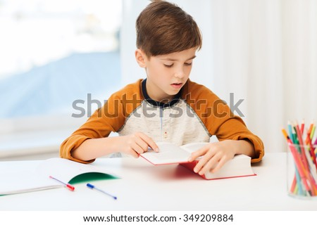 education, childhood, people, homework and school concept - student boy reading book or textbook at home - stock photo