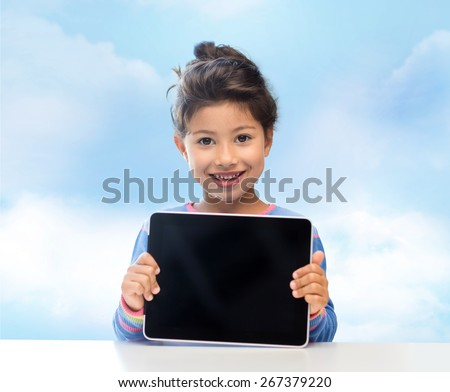 education, children, technology, advertisement and people concept - happy little girl with tablet pc computer over blue sky background - stock photo
