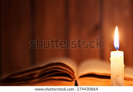 Education concept. Close-up view of old burning candle with shabby old book on wooden background. Focus on the candle - stock photo