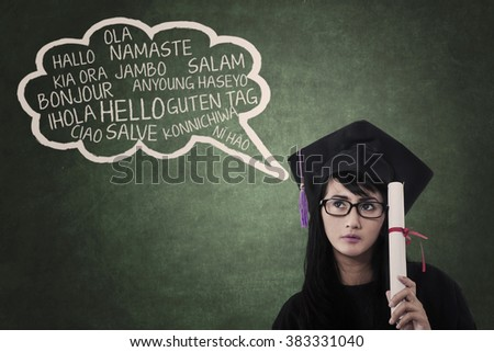 Education concept: female college student in gown learn multilanguage at class - stock photo