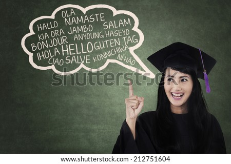Education concept: female college student in gown speaks multi languages  - stock photo