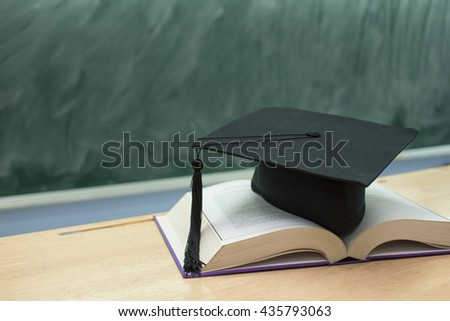 education concept,graduation cap above open book on classroom