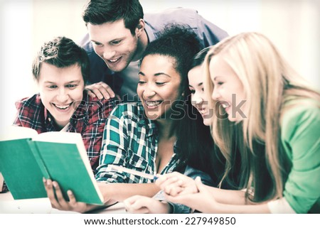 education concept - group of students reading book at school - stock photo