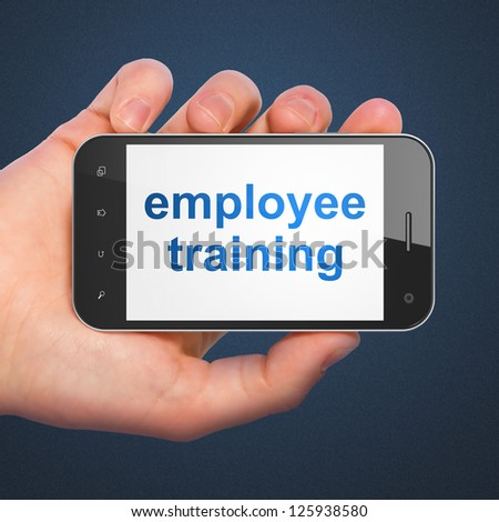 Education concept: hand holding smartphone with word Employee Training on display. Generic mobile smart phone in hand on Dark Blue background. - stock photo