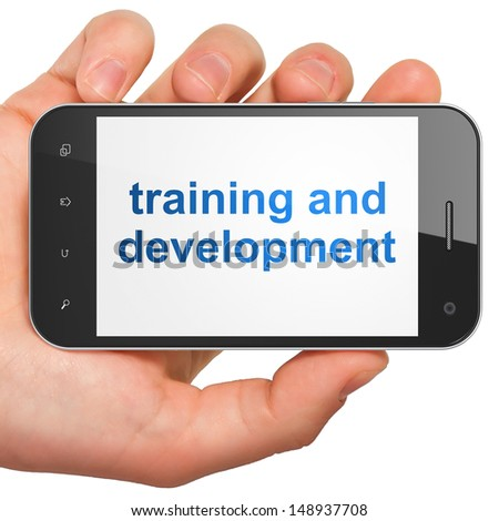 Education concept: hand holding smartphone with word Training and Development on display. Generic mobile smart phone in hand on White background. - stock photo