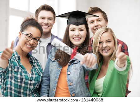 education concept - happy girl in graduation cap with diploma and students - stock photo