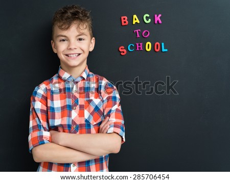 Education concept. Portrait of a schoolboy at the black chalkboard. - stock photo