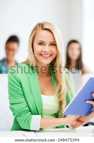 education concept - smiling young girl reading book at school