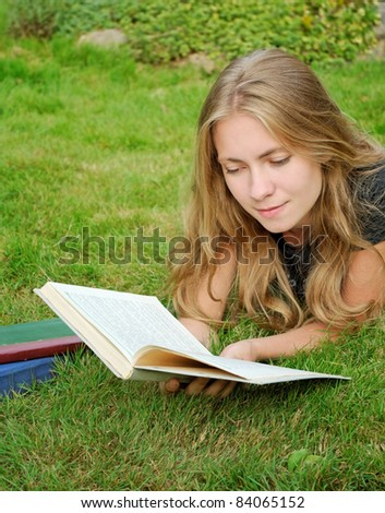 education concept: student girl reading a book in park