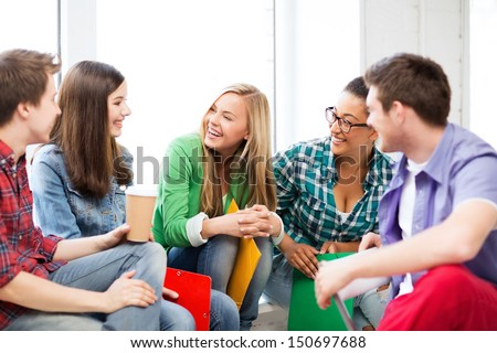 education concept - students communicating and laughing at school - stock photo