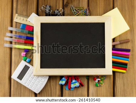Education concept. Top view of blank blackboard with school and office supplies on wooden background - stock photo