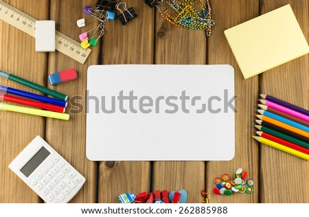 Education concept. Top view of blank sheet of paper with school and office supplies on wooden background - stock photo