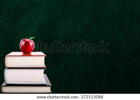 Education concept with apple on stack of books. Isolated on chalkboard background with copy space.