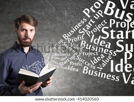 Education concept with businessman standing against concrete wall and holding a book with business related words flying out of it - stock photo
