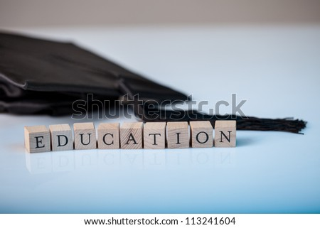 Education concept with the alphabet letters for Education spelt out on wooden blocks beside a graduation cap - stock photo