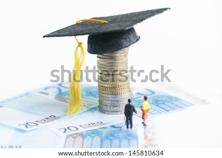 Education cost concept with the miniature man and woman looking at the Mortarboard on top of a stack of Euro coins and 20 Euro banknotes - stock photo
