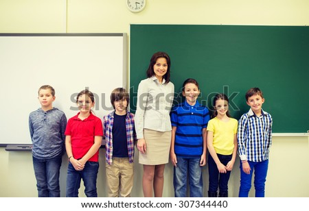 education, elementary, gesture and people concept - group of school kids and teacher in classroom - stock photo