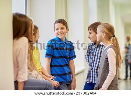 education, elementary school, children, break and people concept - group of smiling school kids talking in corridor - stock photo