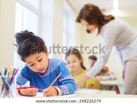 education, elementary school, children, creativity and people concept - happy little girl drawing with coloring pencils over classroom and teacher background - stock photo
