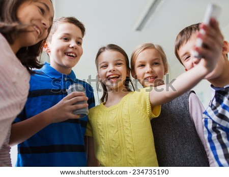 education, elementary school, drinks, children and people concept - group of school kids with smartphone and soda can taking selfie in corridor - stock photo