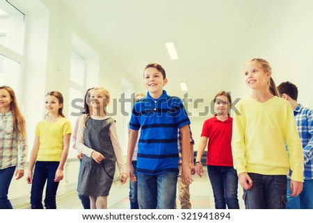 education, elementary school, drinks, children and people concept - group of smiling school kids walking in corridor - stock photo