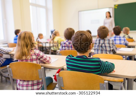 education, elementary school, learning and people concept - group of school kids sitting and listening to teacher in classroom from back - stock photo