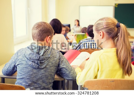 education, elementary school, learning and people concept - group of school kids with notebook writing test and helping in classroom - stock photo
