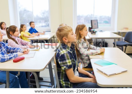 education, elementary school, learning and people concept - group of school kids with notebooks sitting in classroom - stock photo