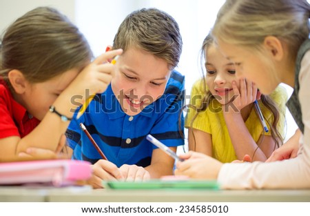 education, elementary school, learning and people concept - group of school kids with pens and papers writing in classroom - stock photo
