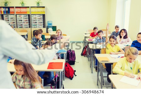 education, elementary school, learning and people concept - group of school kids with teacher sitting in classroom and raising hands - stock photo