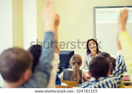education, elementary school, learning and people concept - group of school kids with teacher sitting in classroom and raising hands
