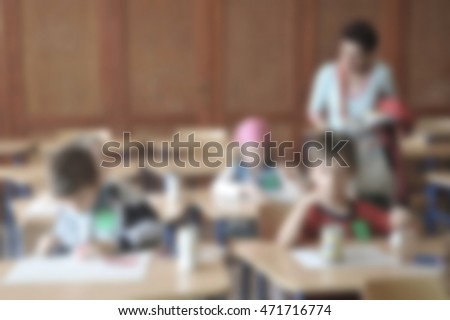 education, elementary school, learning and people concept - group of school kids with teacher sitting in classroom