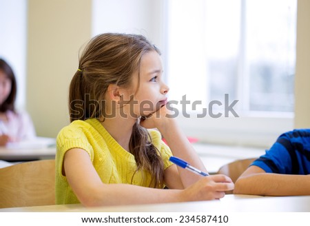 education, elementary school, learning and people concept - school girl with pen being bored in classroom - stock photo