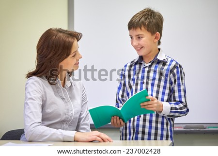 education, elementary school, learning, examination and people concept - school boy with notebook and teacher in classroom - stock photo