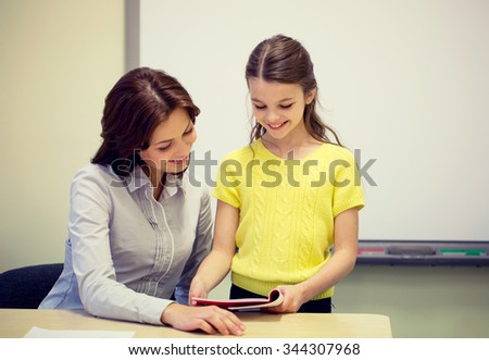 education, elementary school, learning, examination and people concept - school girl with notebook and teacher in classroom - stock photo